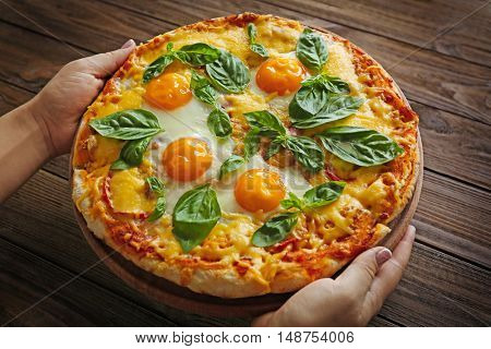 Margarita pizza with basil leaves and egg in female hands on wooden background