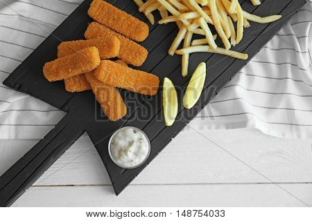 Tasty fish nuggets with lemon, fries and sauce on cutting board