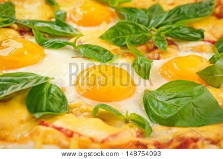 Margarita pizza with basil leaves and egg closeup