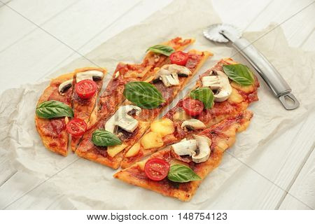 Sliced tasty pizza and cutter on parchment