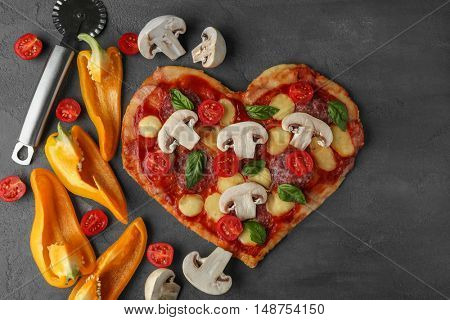 Tasty pizza in heart shape with pepper and tomato slices on table