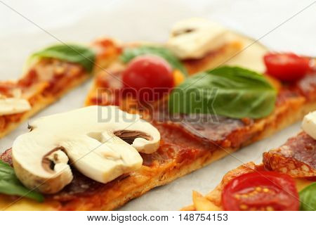 Sliced tasty pizza on parchment, closeup