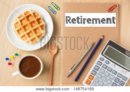 Retirement, text message on paper book and office supplies, pen, coffee on wood desk , copy space / business concept / view from above, top view
