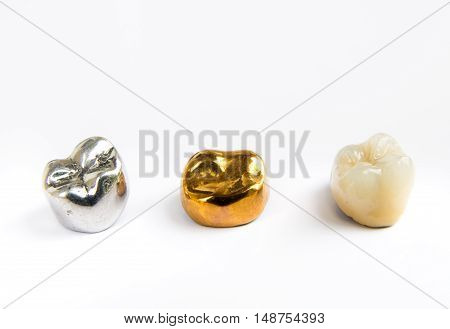 Dental ceramic gold and metal tooth crowns on white background. Isolated.
