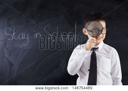 Schoolboy looking through magnifier in the classroom with text Stay in School on the blackboard