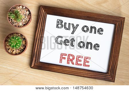buy one get one free, text message on wood frame board on wood table / business concept / Top view