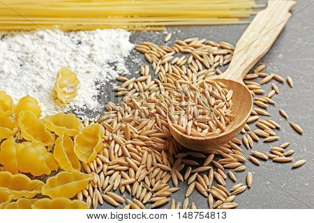 Raw pasta with flour and grains on table