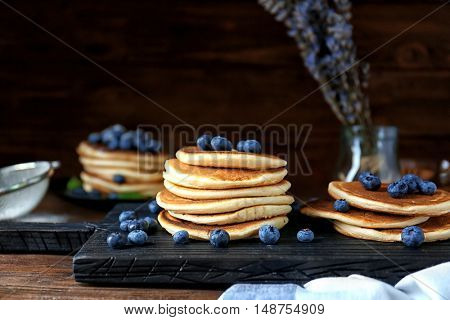 Tasty pancakes with blueberries on cutting board