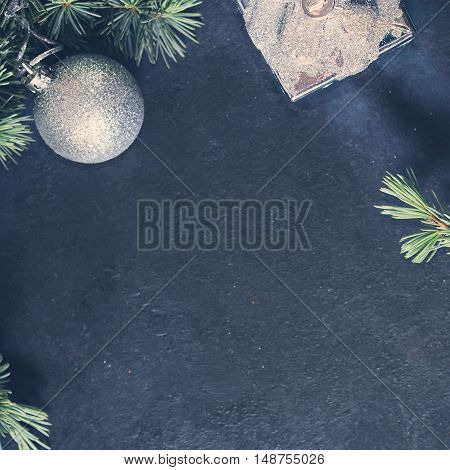 Blue spruce branches with christmas baubles on dark black concrete effect background. Copy space. Square toned image