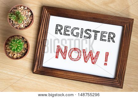 Register now, text message on wood frame board on wood table / business concept / Top view