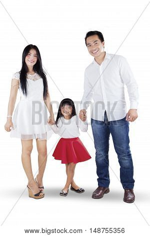 Full length of cheerful Asian family standing in the studio while holding hands and smiling at the camera isolated on white background