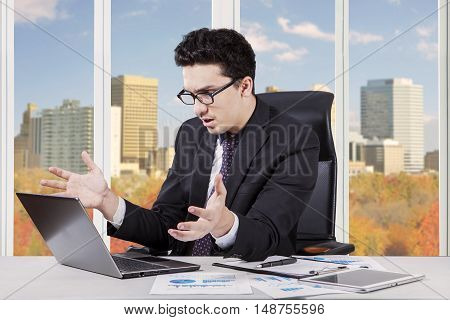 Portrait of caucasian businessman having problem and looks at the laptop in the office