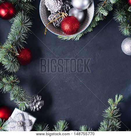 Blue spruce branches with christmas baubles on dark black concrete effect background. Copy space. Square image