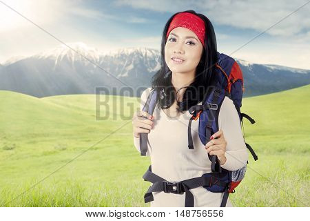 Beautiful female backpacker carrying rucksack on the meadow and smiling at the camera
