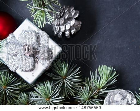 Blue spruce branches with gift-shaped christmas ornament on dark black concrete effect background. Copy space