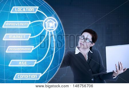 Property value concept with female real estate agent holding a laptop computer and touching property value button on the virtual screen