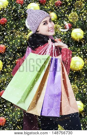 Cheerful female shopper smiling at the camera while carrying shopping bags shot with christmas decoration background