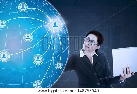 Concept of social network connection. Beautiful female worker holding laptop computer and pressing social network button