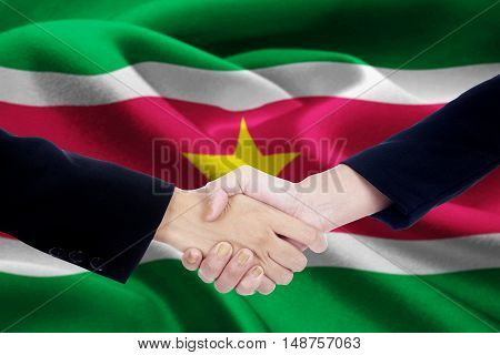 Photo of a friendship handshake with two businesspeople hands closing a meeting and shaking hands in front of a national flag of Suriname