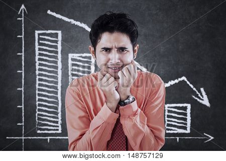 Photo of a frustrated young businessman looks fear and standing in front of declining graph