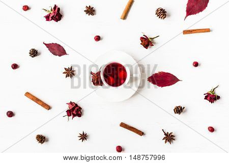 Autumn composition. Cup of fruit tea with autumn leaves cinnamon sticks star anise cones dry roses. Top view flat lay