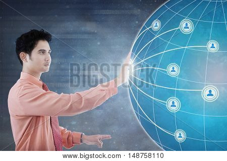 Concept of social network connection. Asian businessman pressing social network icon and globe on the futuristic screen