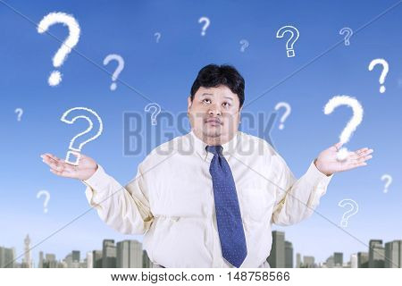 Portrait of overweight businessman looks confused while looking at question mark on the sky
