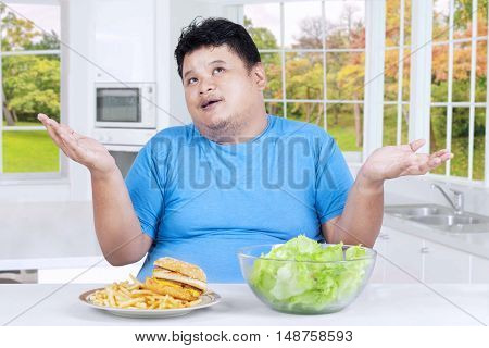 Photo of overweight person sitting in the kitchen while thinking to choose hamburger or salad