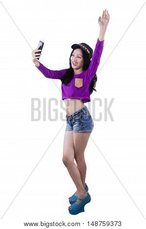 Full length of teenage girl standing in the studio while taking selfie photo with her smartphone isolated on white background