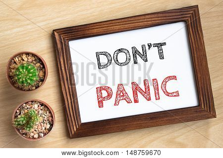 Don't panic, text message on wood frame board on wood table / business concept / Top view