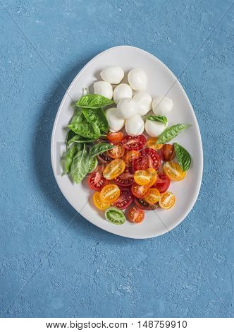 Fresh salad with tomatoes mozzarella and basil. Caprese salad. On a blue background top view
