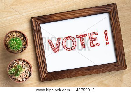 VOTE, text message on wood frame board on wood table / business concept / Top view