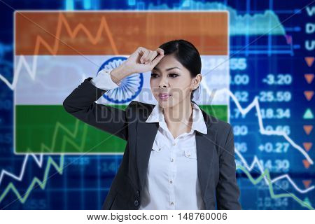 Image of frustrated businesswoman standing in front of declining financial graph and Indian flag