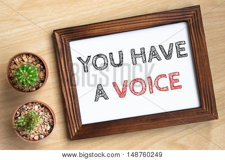 you have a voice, text message on wood frame board on wood table / business concept / Top view