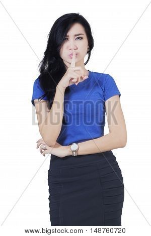 Image of a beautiful young Asian woman making silence gesture isolated on white background