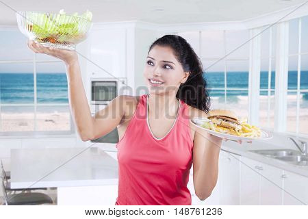 Attractive young woman holding unhealthy and healthy food in the kitchen with beach background on the window