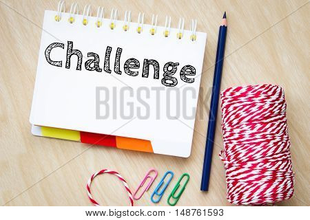 challenge, text message on white paper and pencil on wood table / business concept