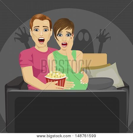 young couple watching horror a movie at home sitting with popcorn on sofa