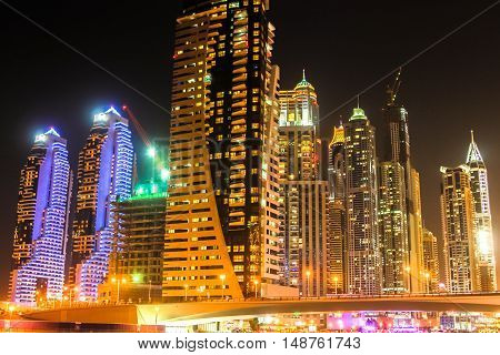 Bridge of Dubai Marina District by night. Dubai Marina is a district in the heart of what is known as New Dubai and is famous for restaurants, luxury clubs and nightlife.