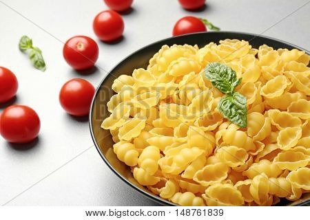 Plate with gnocchi pasta and tomatoes on table, close up