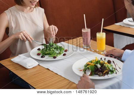 Enjoying tasty food after long day. Close up of couple having lunch in cafe and eating salads, standing on wooden table