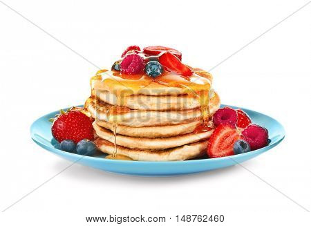 Tasty pancakes with fresh berries and sweet honey on plate, isolated on white