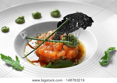 Delicious red fish with sauce on white plate