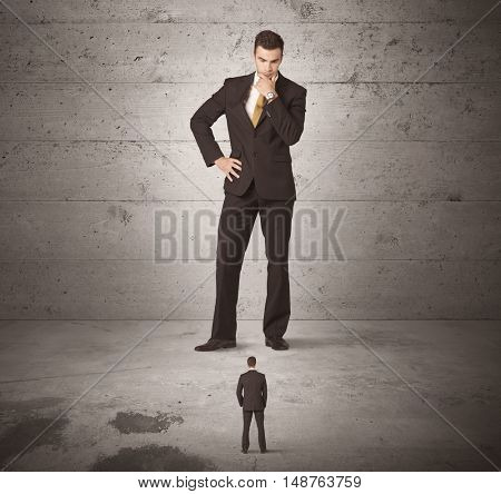 Huge angry business guy looking at small coworker concept on background