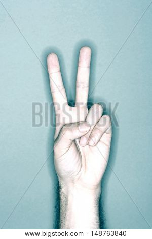 Closeup of a man's hand gesturing peace sign against gray background