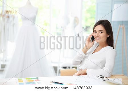 Pretty young dress designer  talking on mobile phone
