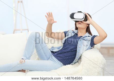 Young woman wearing virtual reality glasses on sofa in a room