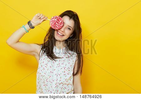 happy modern teenage woman smiling and hiding behind a lollipop candy over yellow background