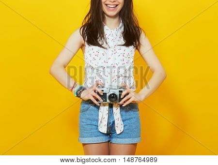 female photographer with vintage old camera. Vivid studio portrait of a hipster girl holding old film camera isolated on yellow background. Cropped unrecognizable