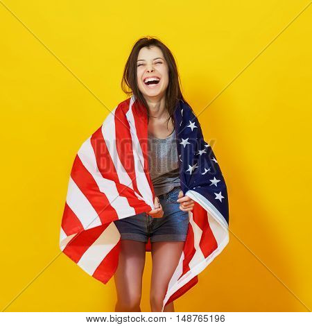 Happy teenage woman with American flag held on back over bright yellow background
